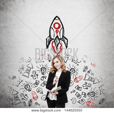 Woman in suit standing near concrete wall with rocket sketch and small icons. Concept of finding problem solution. Mockup