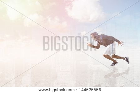 African American man sprinting against big city panorama and cloud in background. Concept of going forward
