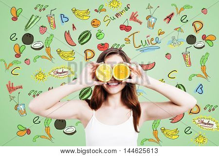 Smiling girl with oranges standing near green wall with fruit sketches. Concept of dieting and good nutrition