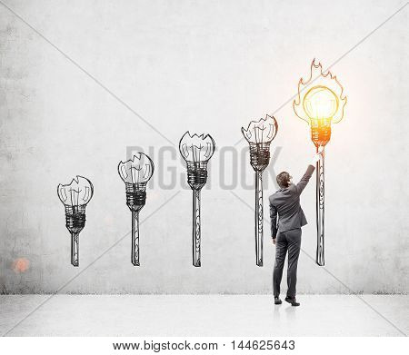 Man in suit lighting torch with shining yellow light bulb. Concrete wall background. Concept of enlightenment.