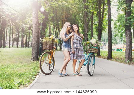 Happy boho chic stylish girls having fun. Beautiful women with bicycles with baskets full of wild flowers. Female friends, youth and happiness, active summer leisure in park concept.