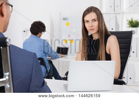 HR department worker looking at camera. Her laptop on desk. Assistant working in corner. Concept of hiring and firing
