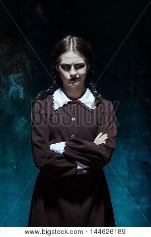 Portrait of a young girl in school uniform as killer woman against school board . The image in the style of Halloween and Addams family