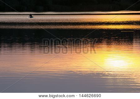 Fisherman on river. Reflection of colorful evening sky in water at sunset. Beautiful summer rural landscape