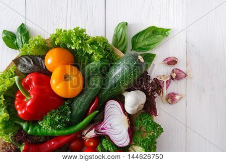 Heap of fresh organic vegetables on white wood background. Healthy natural food abundance on rustic wooden table with copy space. Tomato, lettuce, onion, garlic and other cooking ingredients top view