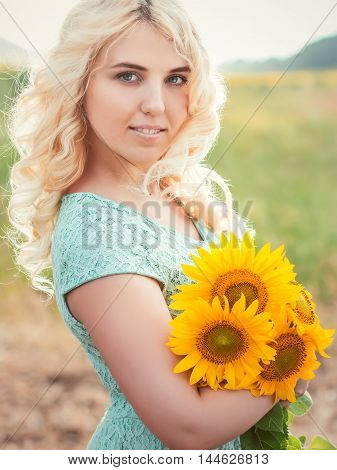 Portrait of a beautiful smiling blonde girl outdoors with sunflowers in hands on a rainy day in sunset