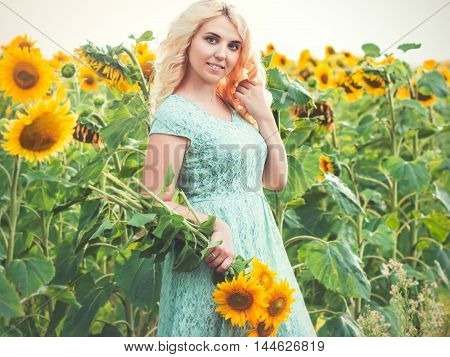 Portrait of a beautiful smiling blonde girl outdoors with sunflowers in hands on a rainy day
