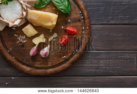 Cheese delikatessen closeup on rustic wood. Wooden desk with parmesan, camembert and brie cuts decorated with garlic, pomegranate and basil, top view image with copy space