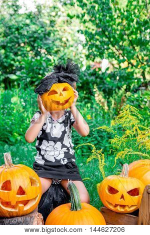 Litlle Girl Is Holding Halloween Pumpkin In Front Of Her Face. Child Dressed In Black Nbetween Jack-