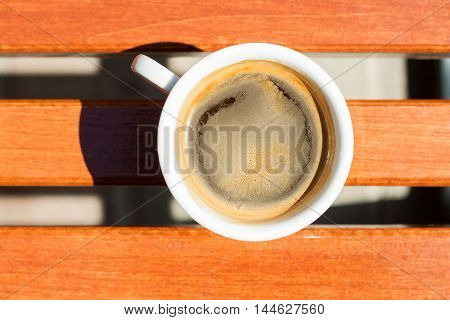 White cup of coffee on a wooden table. The concept of coffee breaks, relaxation, invitations to freshly brewed coffee
