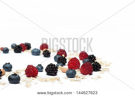 Set for a healthy breakfast isolated on white background. Raspberries, blueberries, blackberries, peanuts and oatmeal.