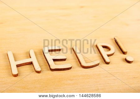 Closeup on wooden background wooden letters Help.