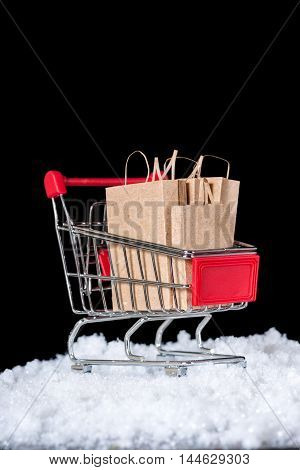 Shopping Trolley With Paper Bags In Snow Is Isolated On Black Background, Copy Space