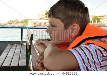 boy in a life jacket sits on a boat on the background of the city