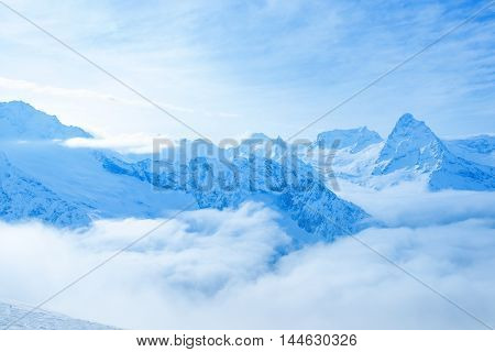 Beautiful Landscape Winter Snow Covered Peaks Of Caucasus Mountain, Dombaj With Clouds And Blue Sky,