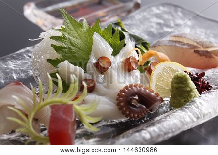 Salad of fresh octopus with wasabi lemon radish and herbs on platter