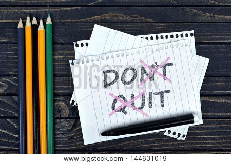 Don't quit text on notepad and office tools on wooden table