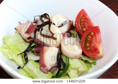 Fresh octopus salad with lettuce tomatoes and seaweed in white bowl