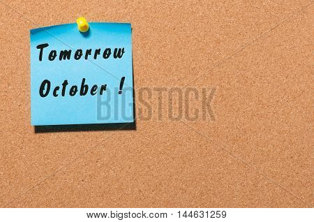 Tomorrow October. hand drawn lettering on color sticker pinned to notice cork board background.