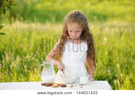 Little girl pouring milk and making cereal breakfast outdoor. Curly kid having breakfast. Healthy lifetime. Summer time