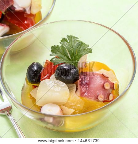 Sauteed octopus with olive onion and tomatoes in glass bowl