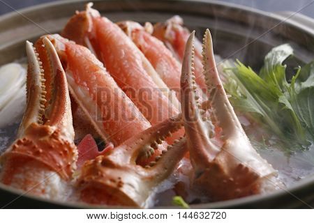 Hot pot of crab claws and legs in big stew with herbs in asian restaurant