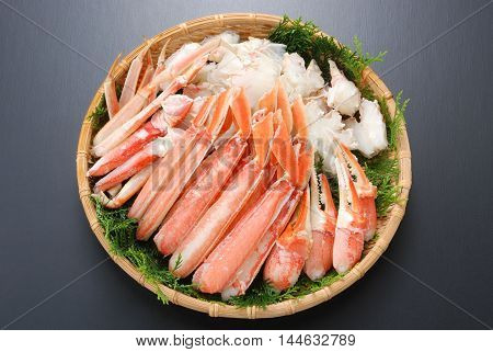 Raw fresh cold snow crab pot set with claws legs meat and herbs on bamboo tray