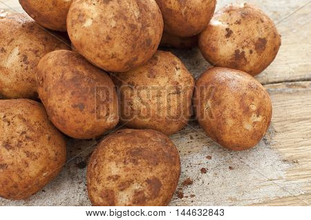 Freshly harvested whole fresh potatoes with adhering dirt in a pile at market on a rustic wooden table