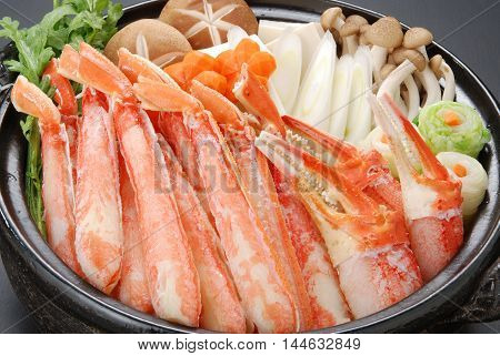 Raw fresh cold snow crab pot set with claws legs mushroom and onion in big black stew