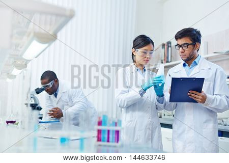 Concentrated Asian female laboratory scientist in safety goggles holding flask with blue liquid showing it to Latin-American colleague writing down results. African-American scientist in background.