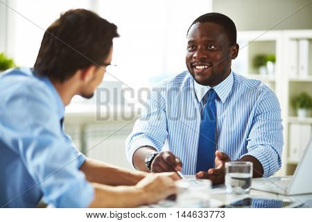 Smiling African-American businessman in shirt and necktie sitting in office talking about work with Caucasian businessman
