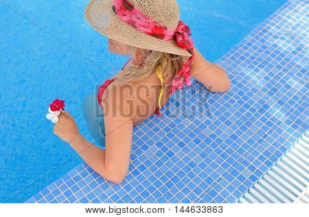 young woman relaxing at the pool on warm summer day