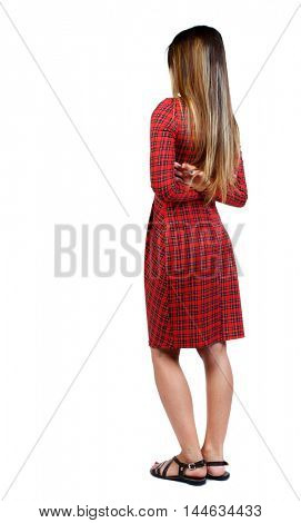 back view of standing young beautiful woman. girl watching. girl in red plaid dress standing sideways with his arms crossed behind his back.