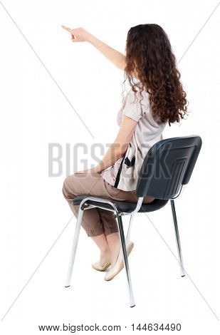 back view of young beautiful woman sitting on chair and pointing. Long-haired curly girl sitting on a chair and pointing to something interesting.