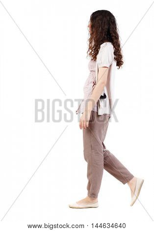 back view of walking curly woman. Long-haired curly girl goes sideways.