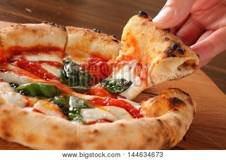 Fried pizza with hot chili and tomatoes sauce on wooden table