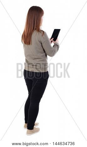 back view of standing young beautiful woman using a mobile phone. girl watching. girl in a gray sweater standing sideways and read e-books.