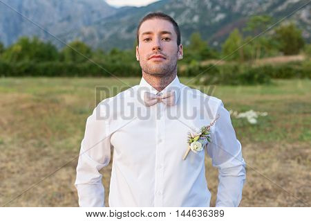Attractive groom is looking forward to the appearance of the bride