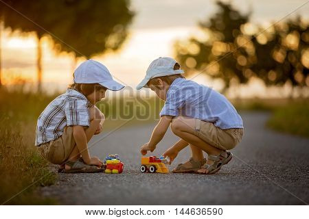Two Children, Boy Brothers, Having Fun Outdoors With Toy Cars