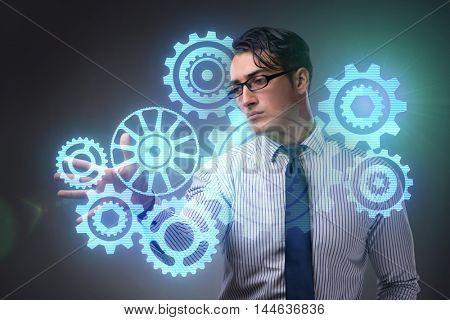 Businessman with cogwheels gear in teamwork concept
