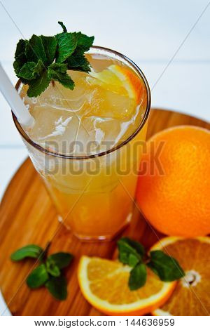 Glass Of Cold Drink With Orange And Mint On Wooden Table. Ice Tea
