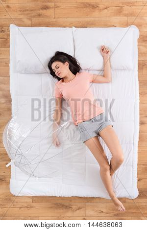Dreams about weather. Top view of merry young woman sleeping on her back on white bed with transparent umbrella and dreaming about future vacation