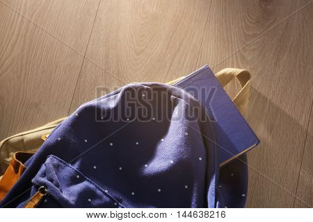 Book with rucksack on wooden background