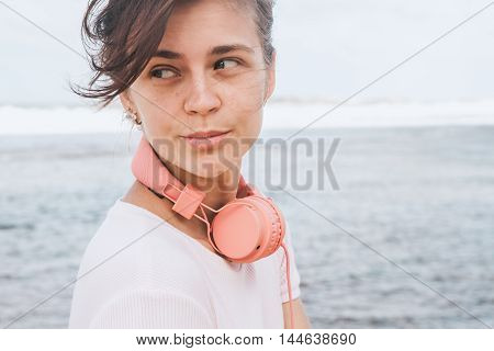 The woman with headphones walking on the beach