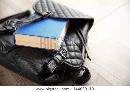 Leather backpack and book on wooden background