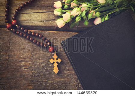 Wooden cross with flowers and Holy Bible, closeup