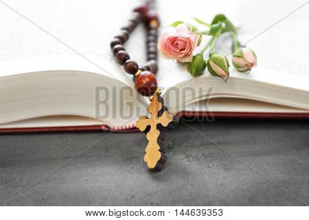 Wooden cross with flowers and Bible  on table closeup