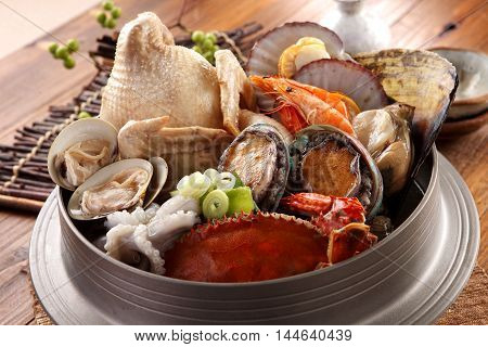 Big hot pot of Tang Emperor of the Sea with fresh octopus abalone crab clams shrimp and chicken on wooden korean table