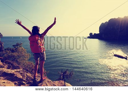 cheering woman hiker open arms at sunset seaside