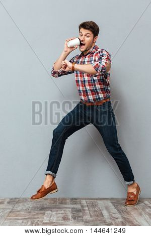 Shocked young man drinking takeaway coffee and running over grey background